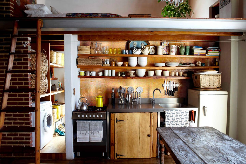 Une magnifique cuisine de style industriel, avec ses murs de briques rouges, son carrelage cuivré et ses poutres apparentes. Découvrez toutes les photos de ce loft Sud Africain dans l'article.