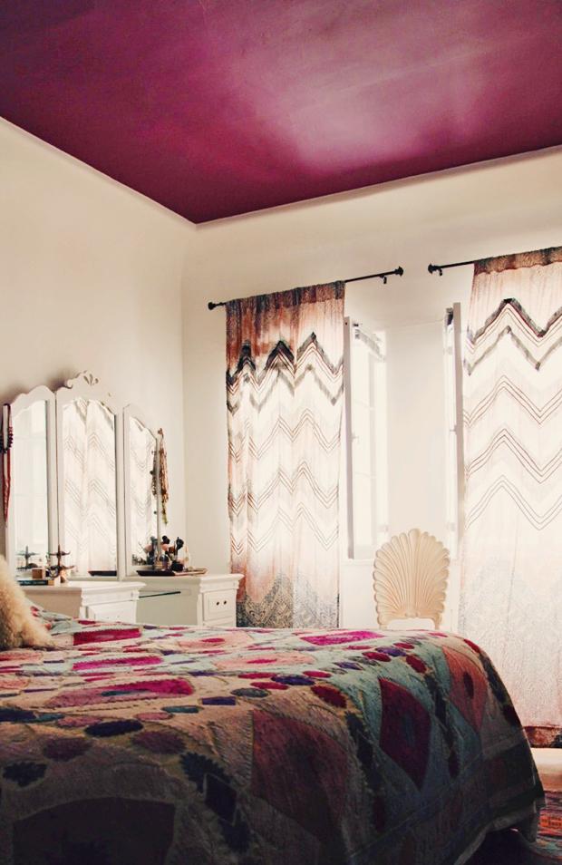 Une jolie chambre au style bohème, avec son magnifique plafond pourpre, ses voilages colorés et ses imprimés ethniques. Découvrez plus d'images de cet intérieur dans l'article.