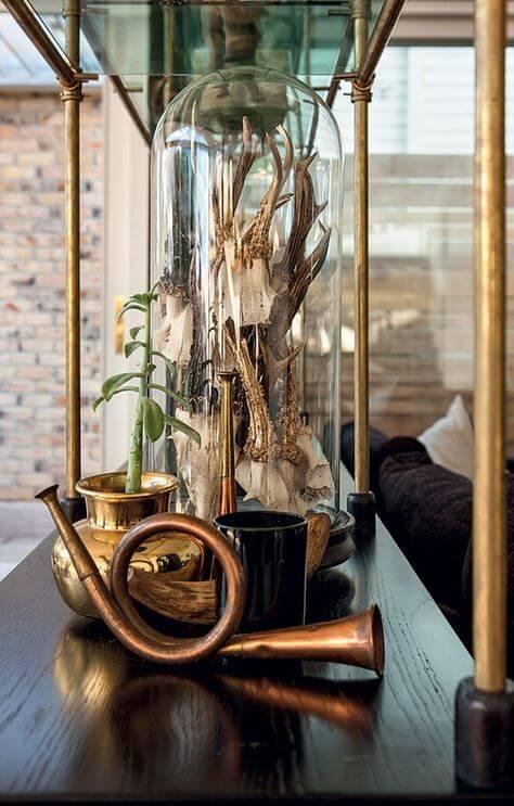 Détail d'un cabinet de curiosité moderne : des instruments de musique en cuivre, des plantes, et des cloches en verre pour abriter des trésors mystérieux. Retrouvez toutes les photos de ce cabinet de curiosité dans l'article !