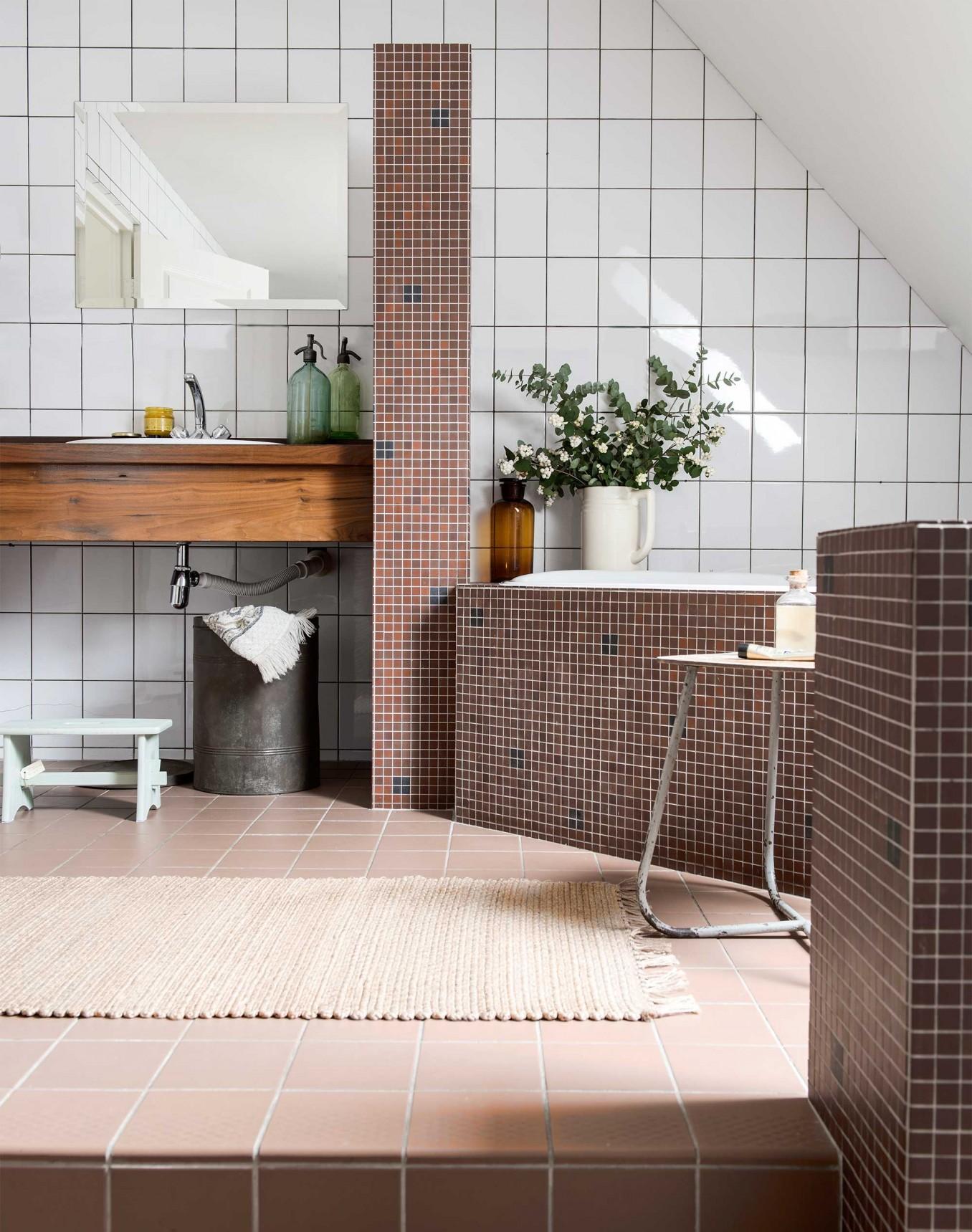 Une très belle salle de bain et ses petits carreaux de mosaïque cuivrée. Découvrez plus de photos de cet intérieur rustique chic dans l'article.