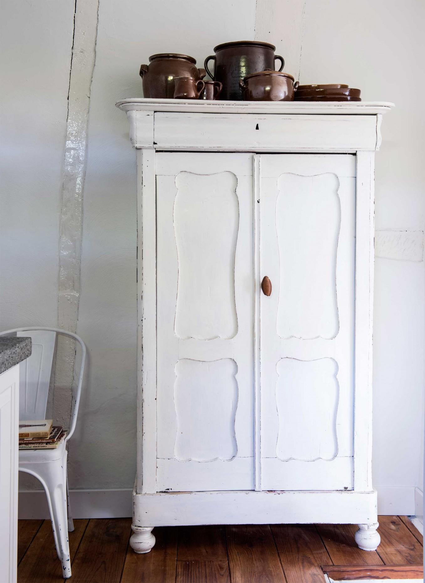 Un garde à manger rétro, tout simplement repeint en blanc et qui affiche une jolie collection de pots en grès vintage. Découvrez toutes les images de cette maison rustique chic dans l'article.