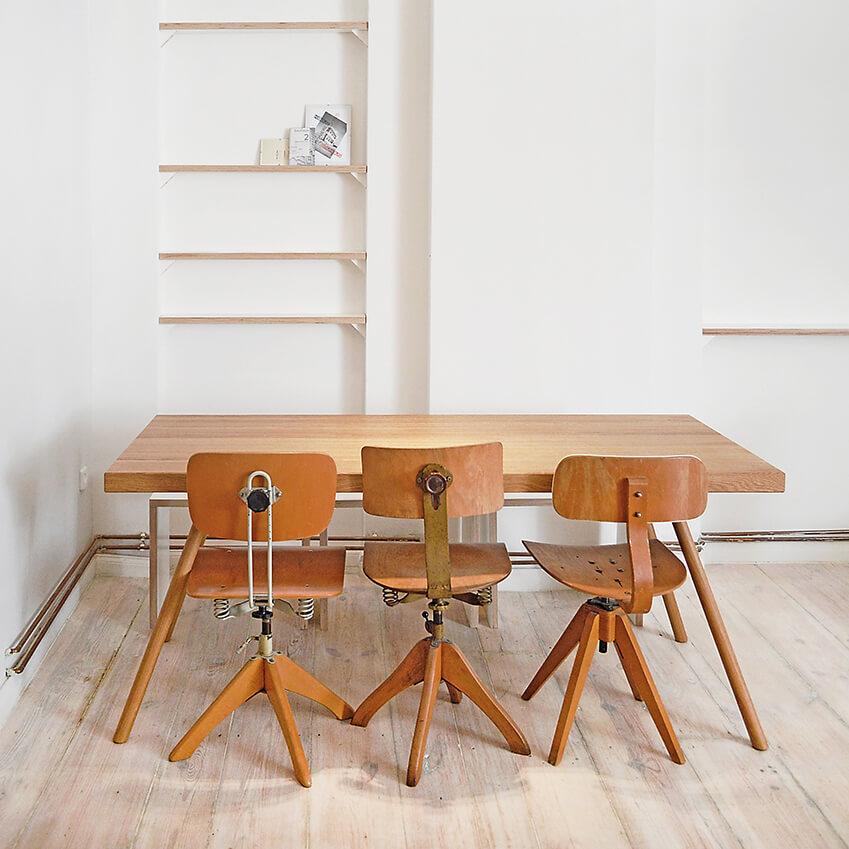 Une salle à manger minimaliste, avec cette belle table en bois naturel et ces chaises légèrement dépareillés. Retrouvez plus de photos du salon et de la cuisine dans l'article !