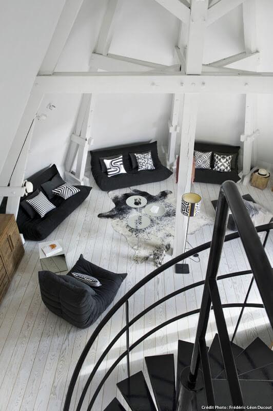 Un incroyable volume sous les toits, transformé en salon minimaliste. Retrouvez toutes les photos de ce loft industriel dans l'article.
