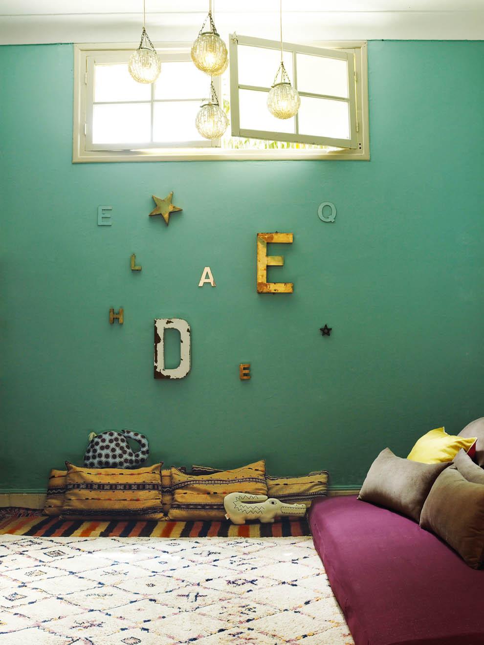 Un joli salon marocain, avec un tapis moelleux, des coussins colorés au sol et une jolie déco bohème sur un beau mur turquoise. Découvrez plus d'inspiration déco dans l'article !