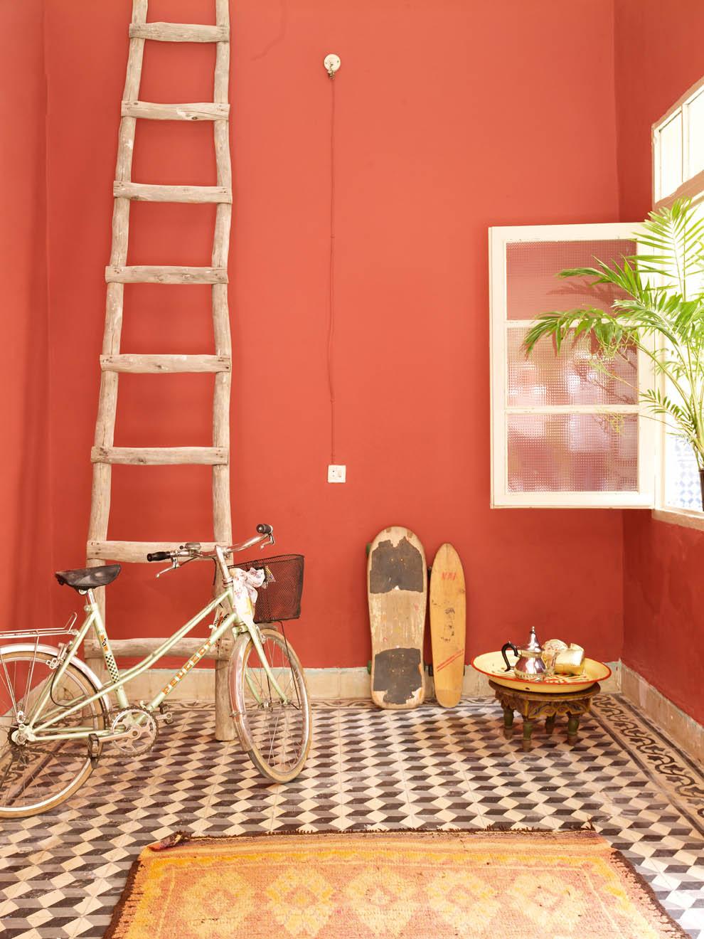 Une jolie terrasse d'inspiration marocaine, avec ses murs peints en corail vif et une jolie mosaïque en noir et blanc. Découvrez plus de photos de cette terrasse marocaine dans l'article !