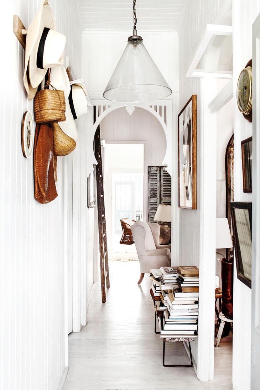 Un hall d'entrée lumineux, aux murs blancs, et décorés avec de beaux objets chinés