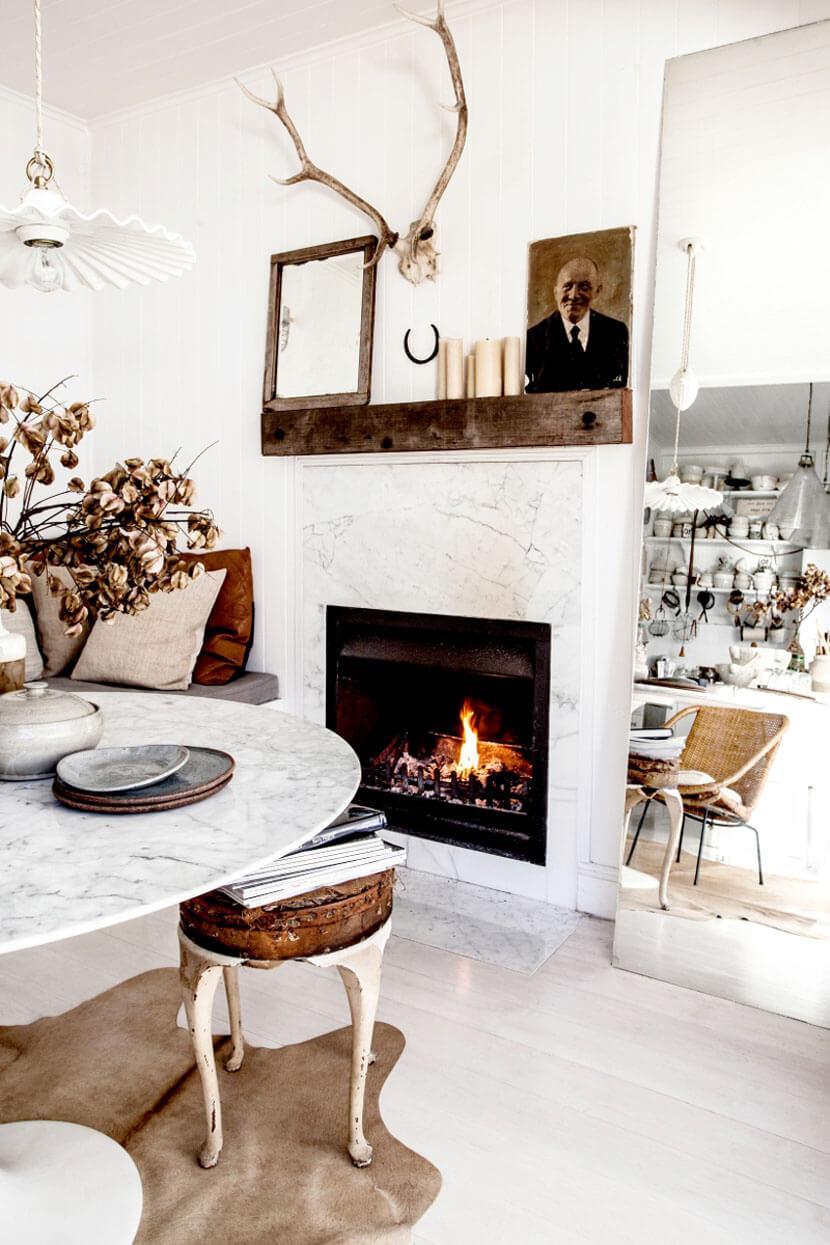 Un salon rustique chic, avec cette belle cheminée en marbre et ses objets vintages
