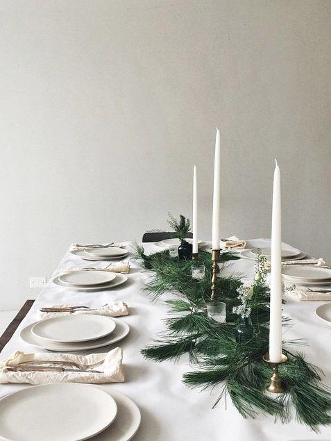 Idée déco pour une table de noel blanche, décorée de bougies et chandeliers dorés
