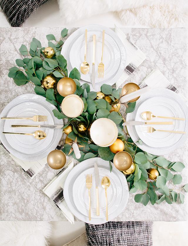 Idée décoration avec cette table de Noel moderne, décorée de touches dorées et de feuilles d'eucalyptus