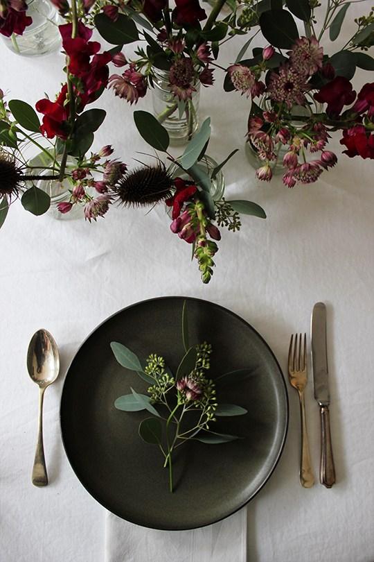 Une table de Noel naturelle et rustique avec une nappe en lin et un bouquet de fleurs bordeaux