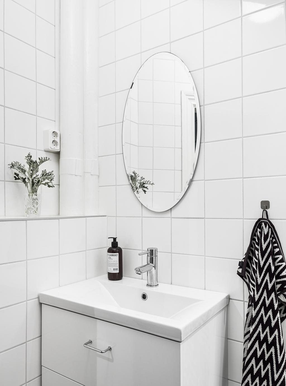 Déco d'une salle de bain blanche, avec un miroir rond et du carrelage blanc