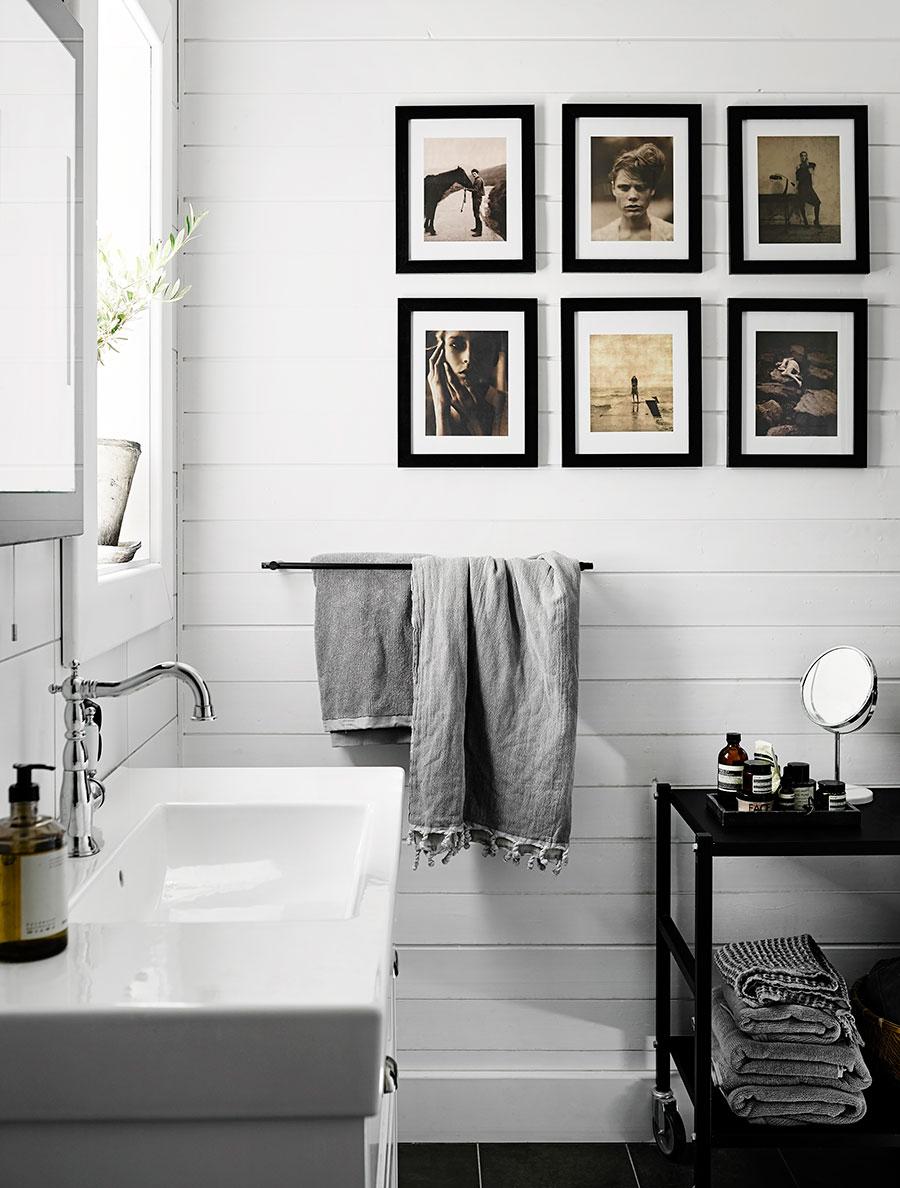Une déco scandinave dans la salle de bain, avec des tableaux accrochés au murs et des tissus en lin