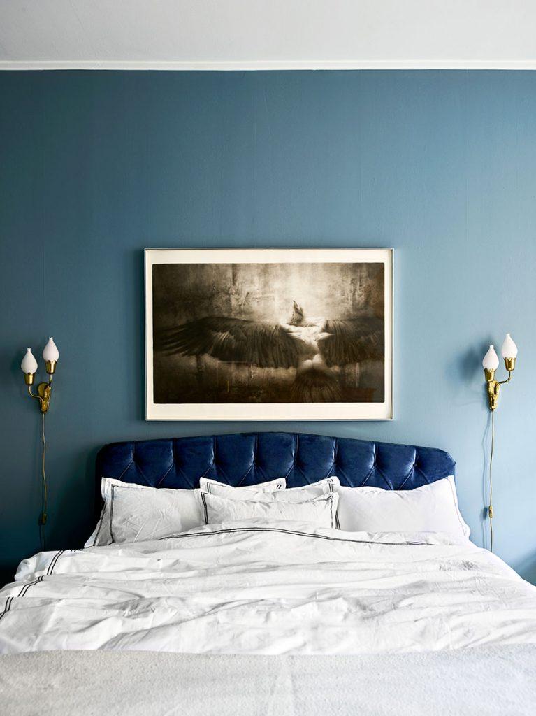 Une déco originale pour cette chambre aux murs bleu canard et à la tete de lit matelassée