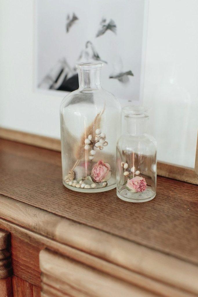 Placer des fleurs séchées dans une petite bonbonne en verre